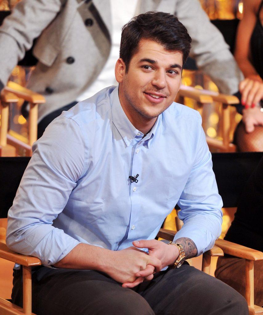 Rob Kardashian purtând o cămașă albastră în timp ce stă pe un scaun și zâmbește la cameră la emisiunea Dancing With The Stars