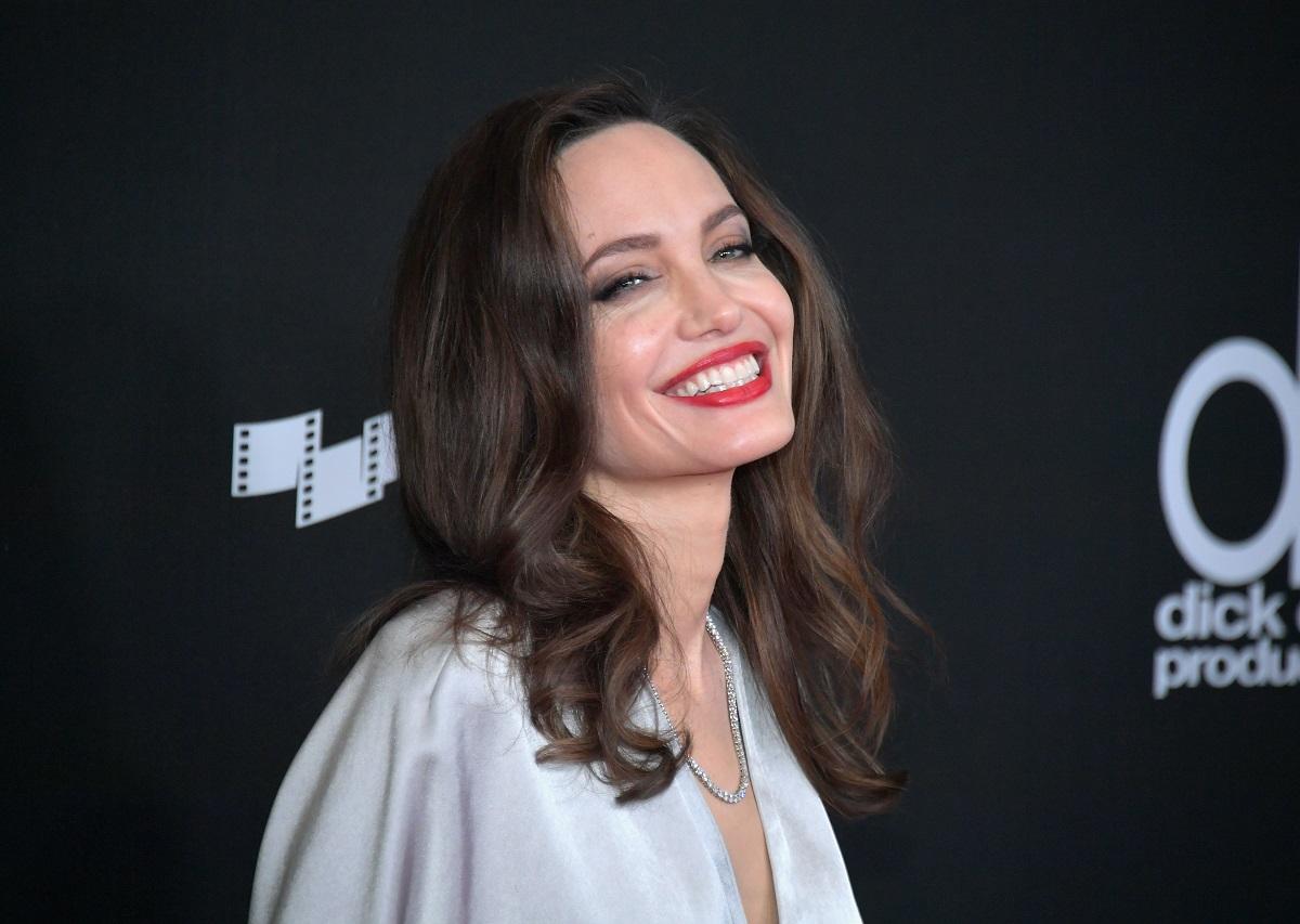 Angelina Jolie purtând o rochie albă și un ruj roșu în timp ce participă la o ceremonie de la Hollywood în anul 2017