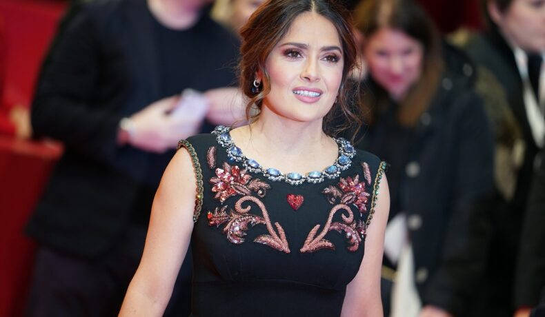 Actrița Salma Hayek zâmbind la cameră pe covorul roșu în timp ce poartă o rochie neagră cu broderie cu flori în zona bustului