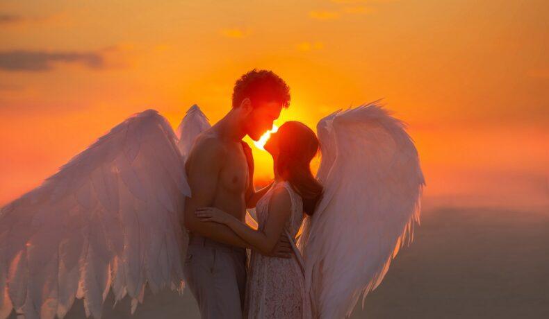 Un cuplu de îndrăgostiți care se țin în brațe și se privesc în ochi în timp ce soarele apune peste aripile lor de îngeri