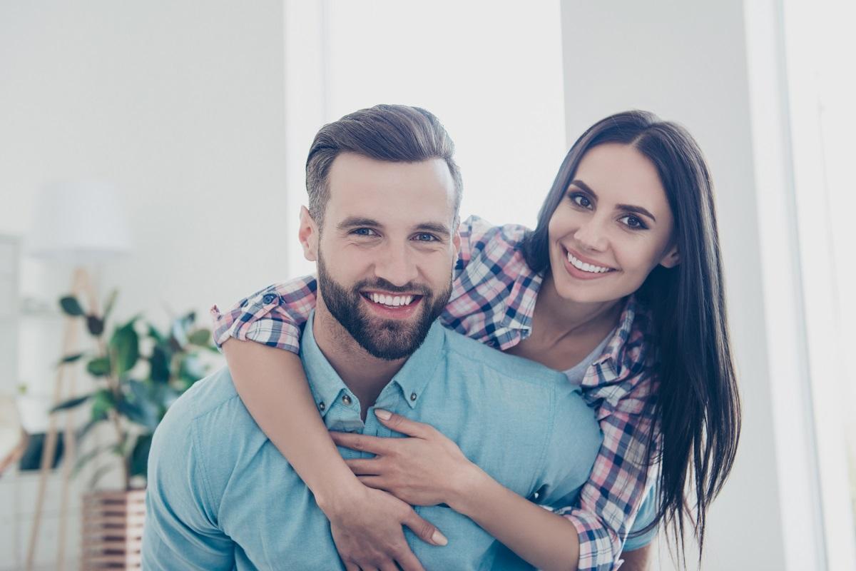 Un bărbat cu barbă și tricou albastru care este ținut în brațe după umeri de iubita sa cu părul lung și brunet demonstrându-i unul din semnele unei relații sănătoase de cuplu