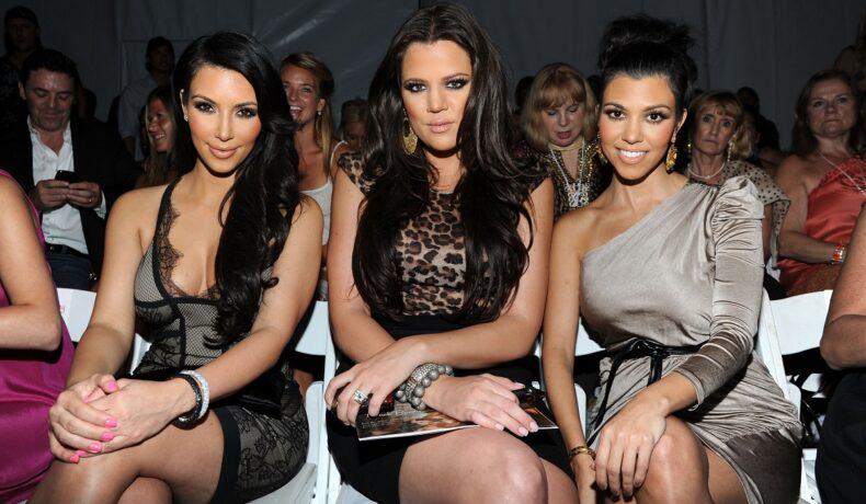 Surorile Kardashian, Kim Kardashian, Khloe Kardashian și Kourtney Kardashian în timp ce stau pe scaune și sunt îmbrăcate elegant la un eveniment public din anul 2014