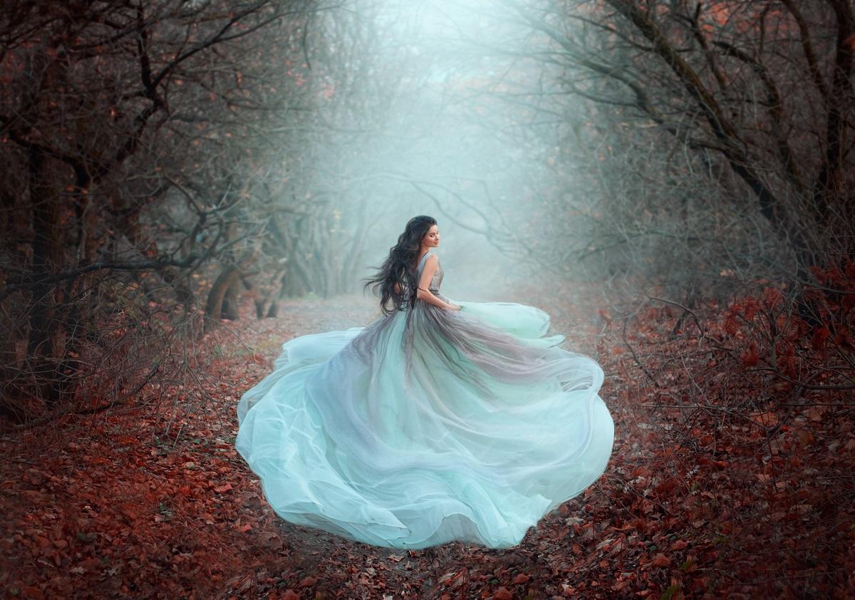 O femeie frumoasă într-o rochie superbă, vapăroasă de culoare alb în timp ce aleargă printr-o pădure în timpul toamnei pentru a reprezenta una din acele zodii care nu sunt făcute pentru căsătorie