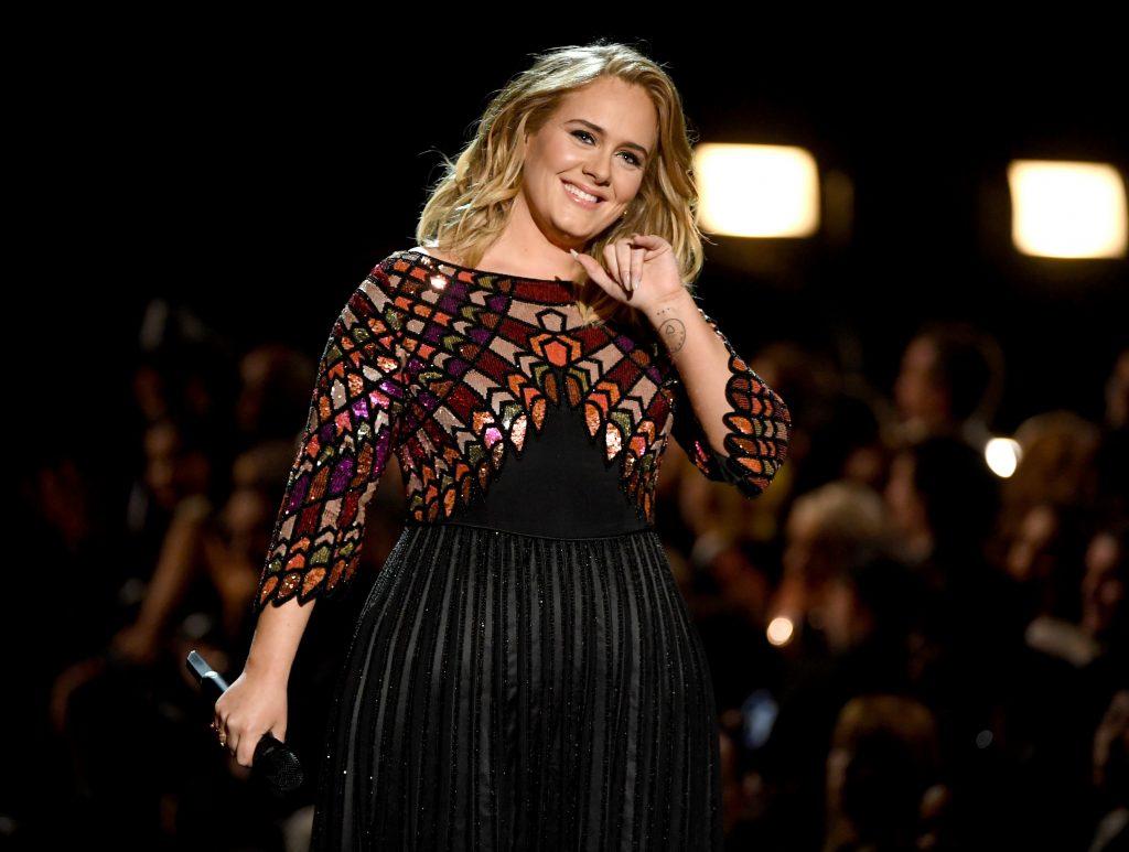 Adele, pe scena Premiilor Grammy la cea de-a 59-a ediție a evenimentului. Artista a îmbrăcat o rochie neagră, cu aplicații aurii și argintii pe umeri