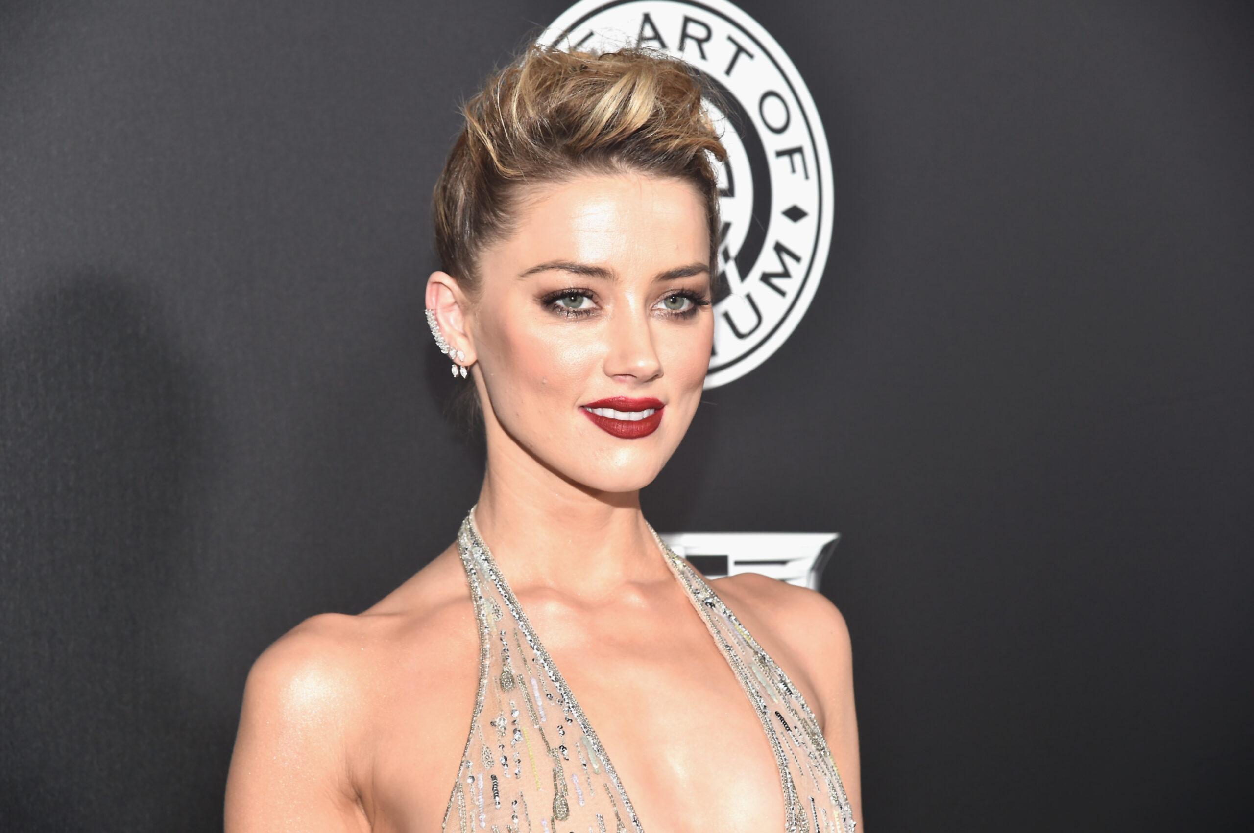 Amber Heard a apărut la Art of Elysium, în 2018, cu un look dramatic. Părul strâns, machiaj închis la culoare, decolteu adânc, rochie argintie