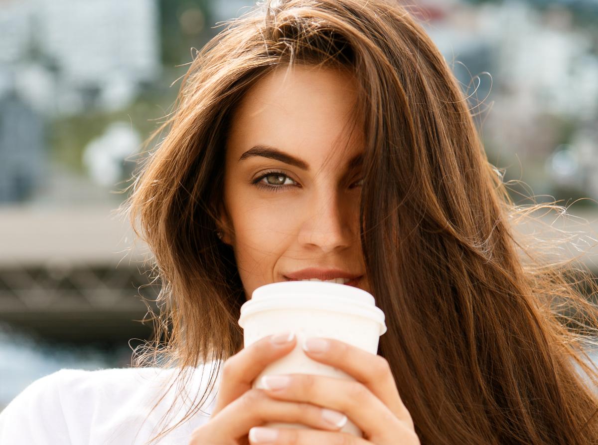 O femeie frumoasă, cu părul lung, ține în mâini un pahar alb de unică folosință, în care se află cafea.