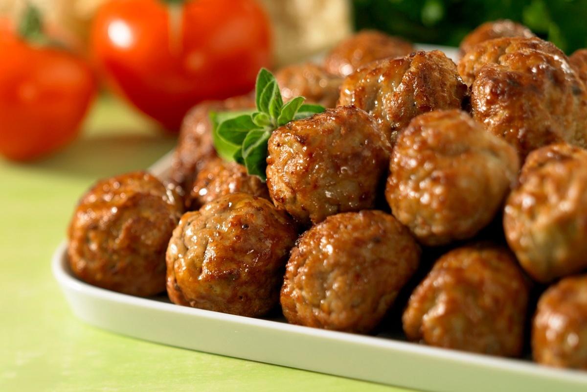 Chiftele din carne cu legume pe un platou alb, alături de roșii