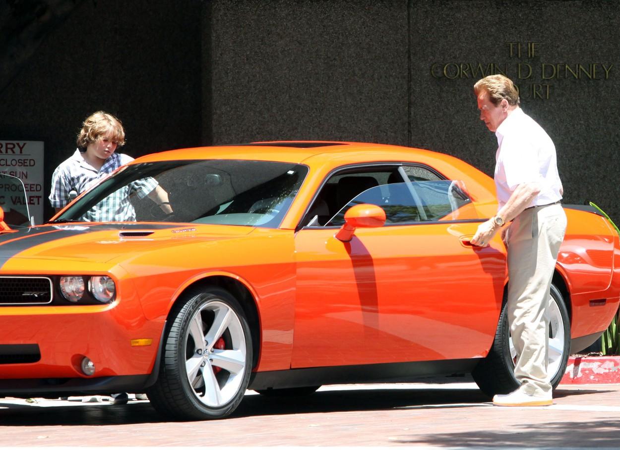 Christopher Schwarzenegger și Arnold, în timp ce se urcă într-o mașină portocalie, în anul 2009, în Brentwood