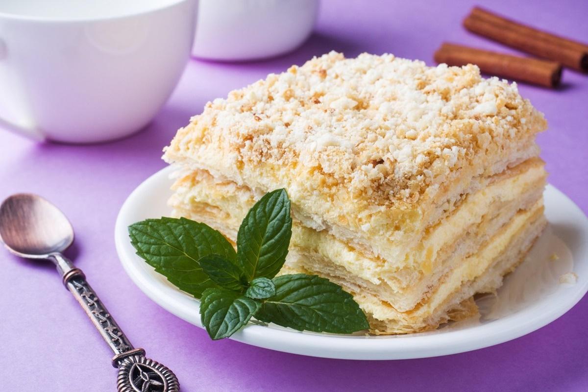 Porție din prăjitura cremșnit cu cremă de vanilie pe o farfurie albă