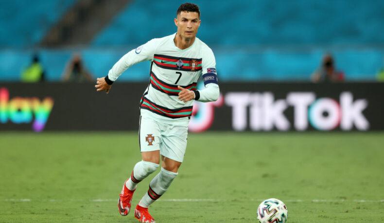 Cristiano Ronaldo, pe terenul de forbal, în timp ce șutează mingea, la meciul Belgia vs. Portugalia, în timpul UEFA Euro 2020