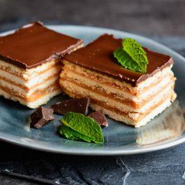 Două porții de prăjitură fără coacere cu biscuiți și cremă caramel pe o farfurie gri