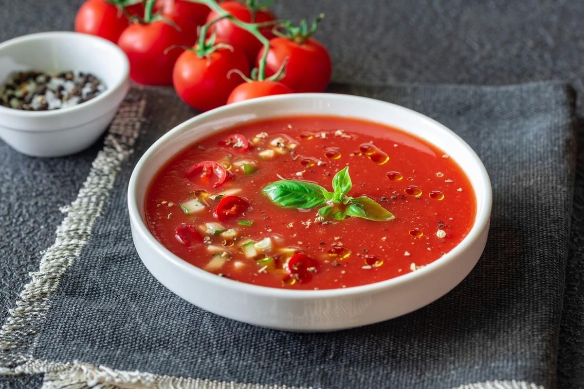 Porție de gazpacho într-un bol alb, alături de roșii proaspete
