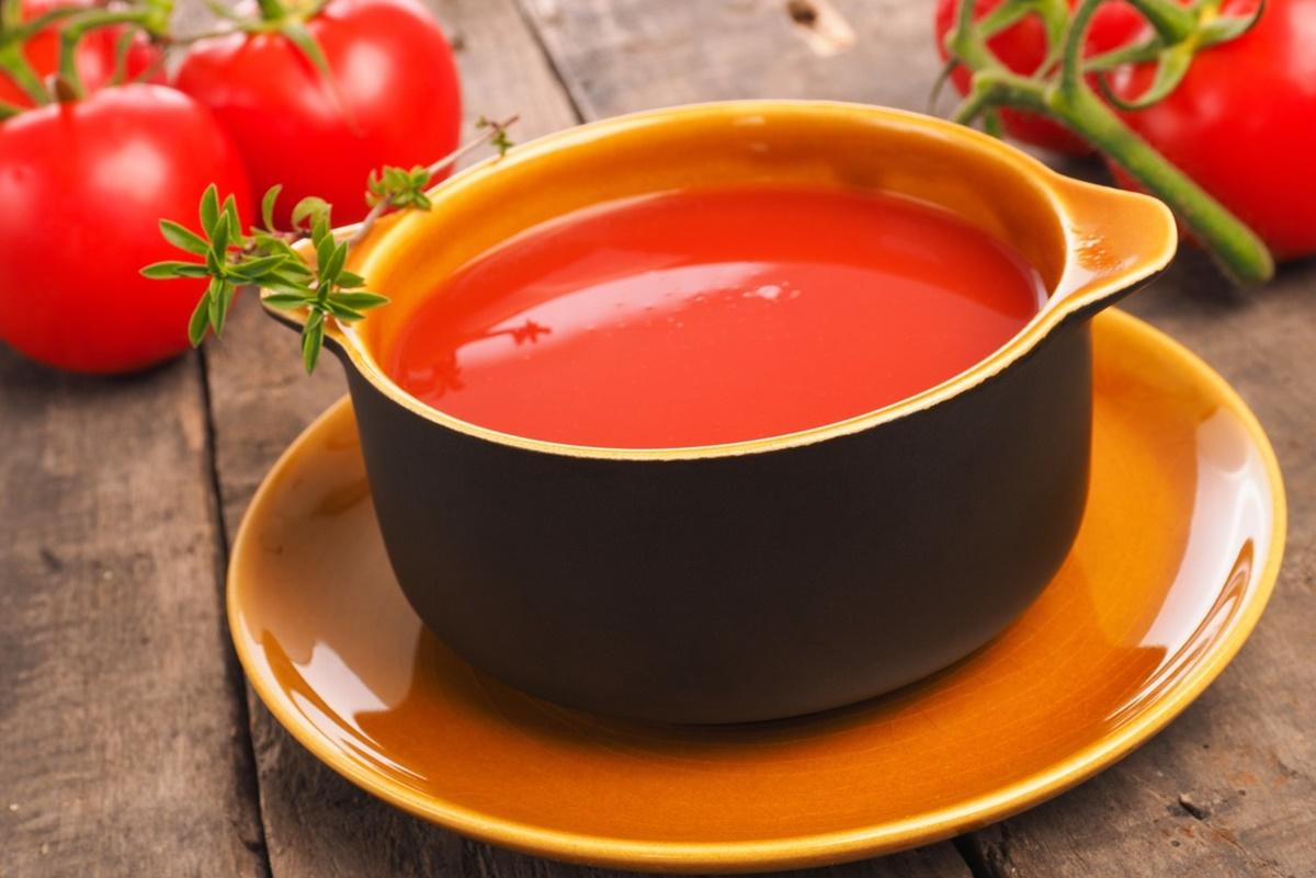 Supa Gazpacho într-un bol rustic așezat pe o farfurie portocalie