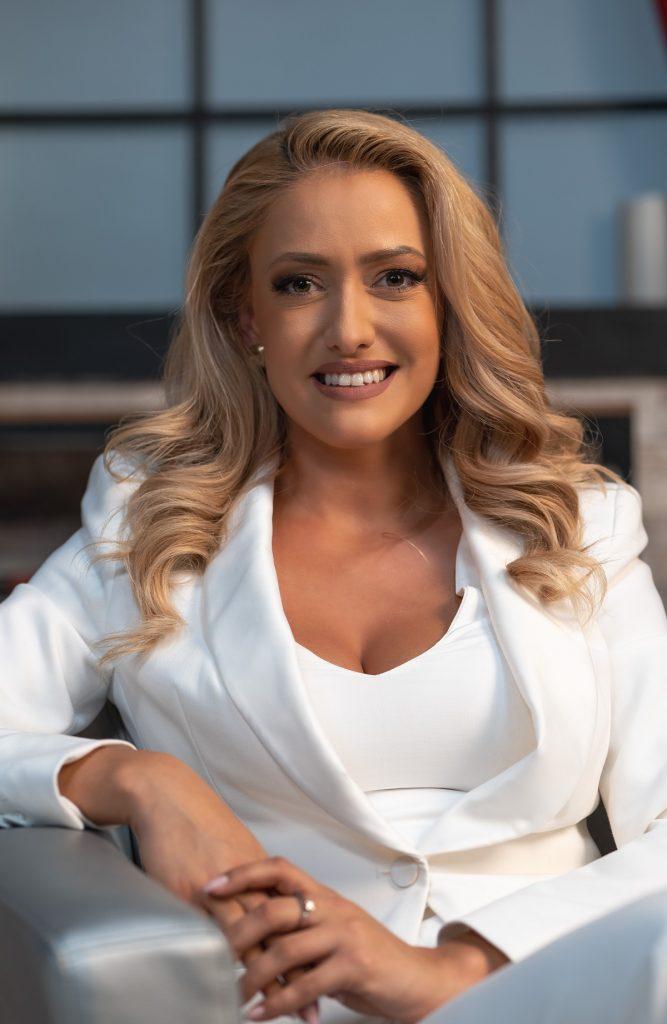 Portret al prezentatoarei știrilor de matinal Iuliana Pepene în timp ce zâmbește la camerele de fotografiat