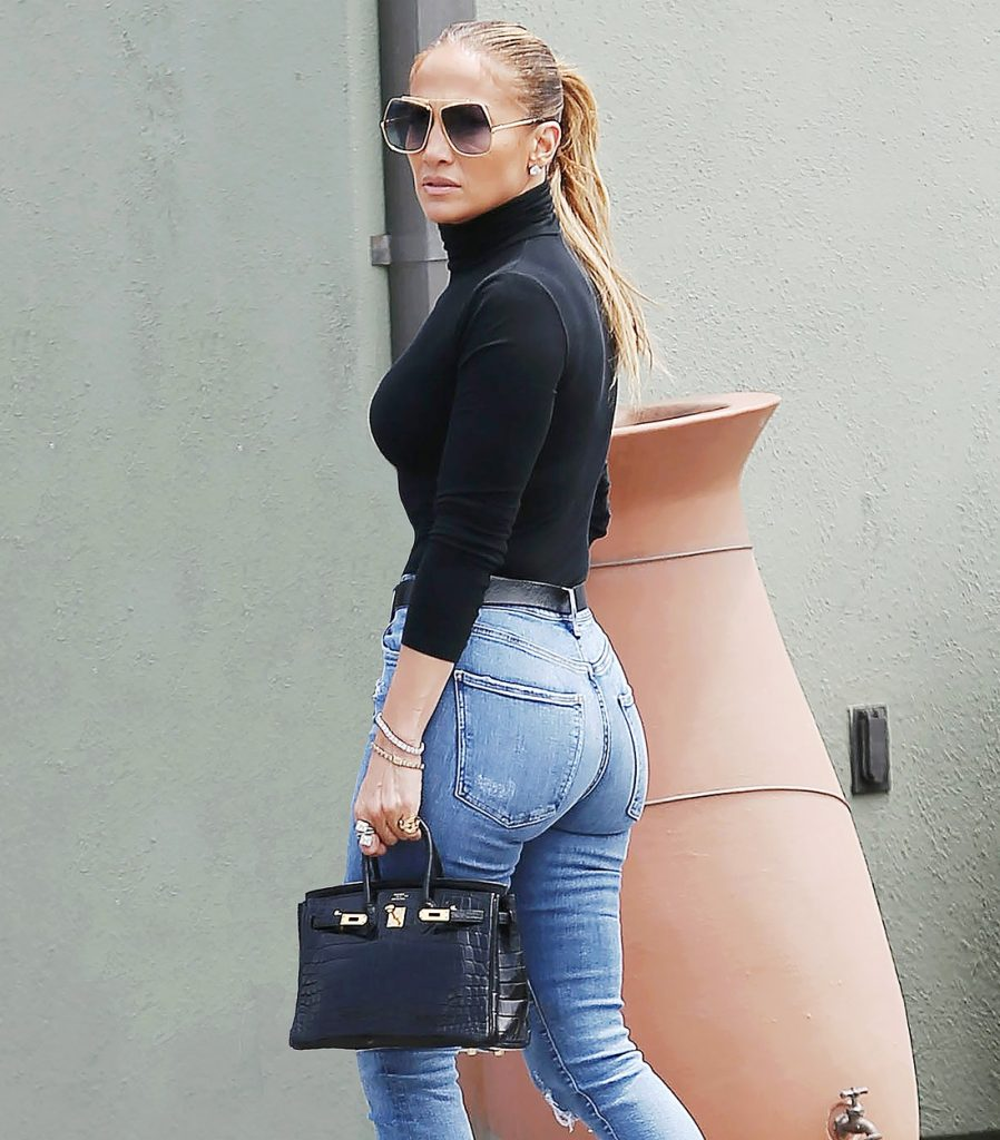 Jennifer Lopez, într-o pereche de jeanși, cu o maletă neagră și ochelari mari de soare