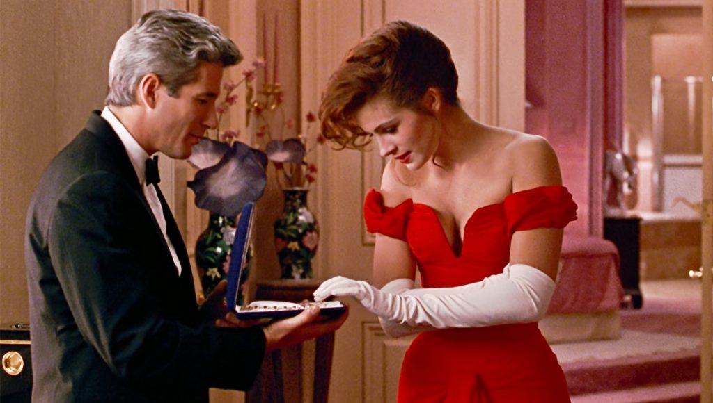 Julia Roberts și Richard Gere în filmul Pretty Woman, din 1990. Scena în care el îi oferă colierul. Gere e imbrăcat în costum negru, Julia poartă rochia roșie decoltată și mănuși albe, în camera de hotel