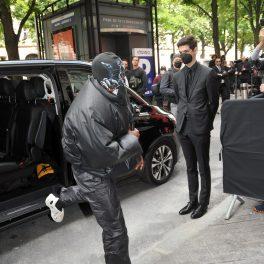 Kanye West, cu o cagulă pe cap, în timp ce iese din mașină, pentru a intra la show-ul Balenciaga 2021