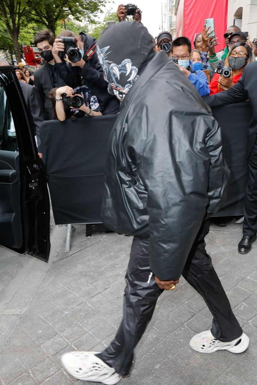 Kanye West, pozat în timp ce iese dintr-o clădire, îmbrăcat în negru, cu cagulă pe cap