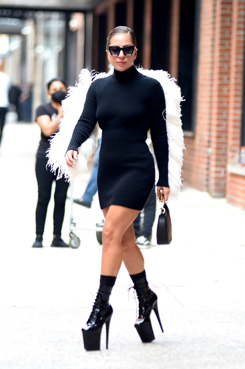 Lady Gaga, surprinsă pe stradă din New York, SUA; întro rochie neagră, cu pene albe, aripi de înger și pantofi foarte înalți. Fundal de stradă, cu trotuar gri