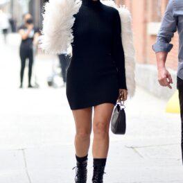 Lady Gaga a fost surprinsă pe stradă din New York, SUA; întro rochie neagră, cu pene albe, aripi de înger și pantofi foarte înalți. Fundal de stradă, cu trotuar gri, cu mâna ridicată și geantă neagră