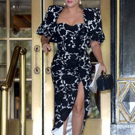 Lady Gaga, într-o rochie alb cu negru, cu umeri mari, la ieșirea unui hotel din New York