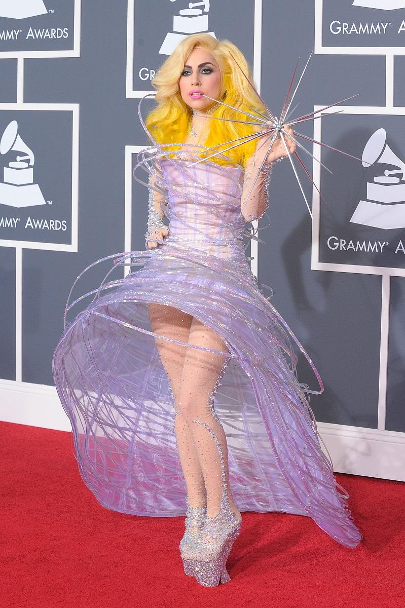 Lady Gaga pe covorul roșu la Premiile Grammy, cea de-a 52-a ediție. A purtat o rochie mov, cu cercuri mari, părul foarte blond și pantofi înalți care sclipesc. Fundal roșu și gri