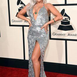 Lady Gaga pe covorul roșu la cea de-a 57-a ediție a Premiilor Grammy, anul 2015. Lady Gaga pe covorul roșu, rochie argintie, mulată, cu decolteu adânc. Părul blond, aproape alb, fundalul alb cu negru și roșu