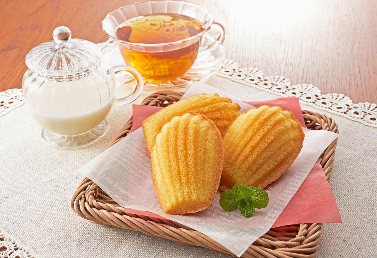 Madeleine cu lămâie, alături de un ceainic și un recipient cu lapte