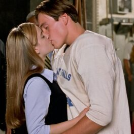 Mena Suvari și Chris Klein în filmul American Pie, sărutându-se. În film, ei au avut o relație și aici au fost surprinși când se sărutau, el într-o bluză albă, ea în uniformă