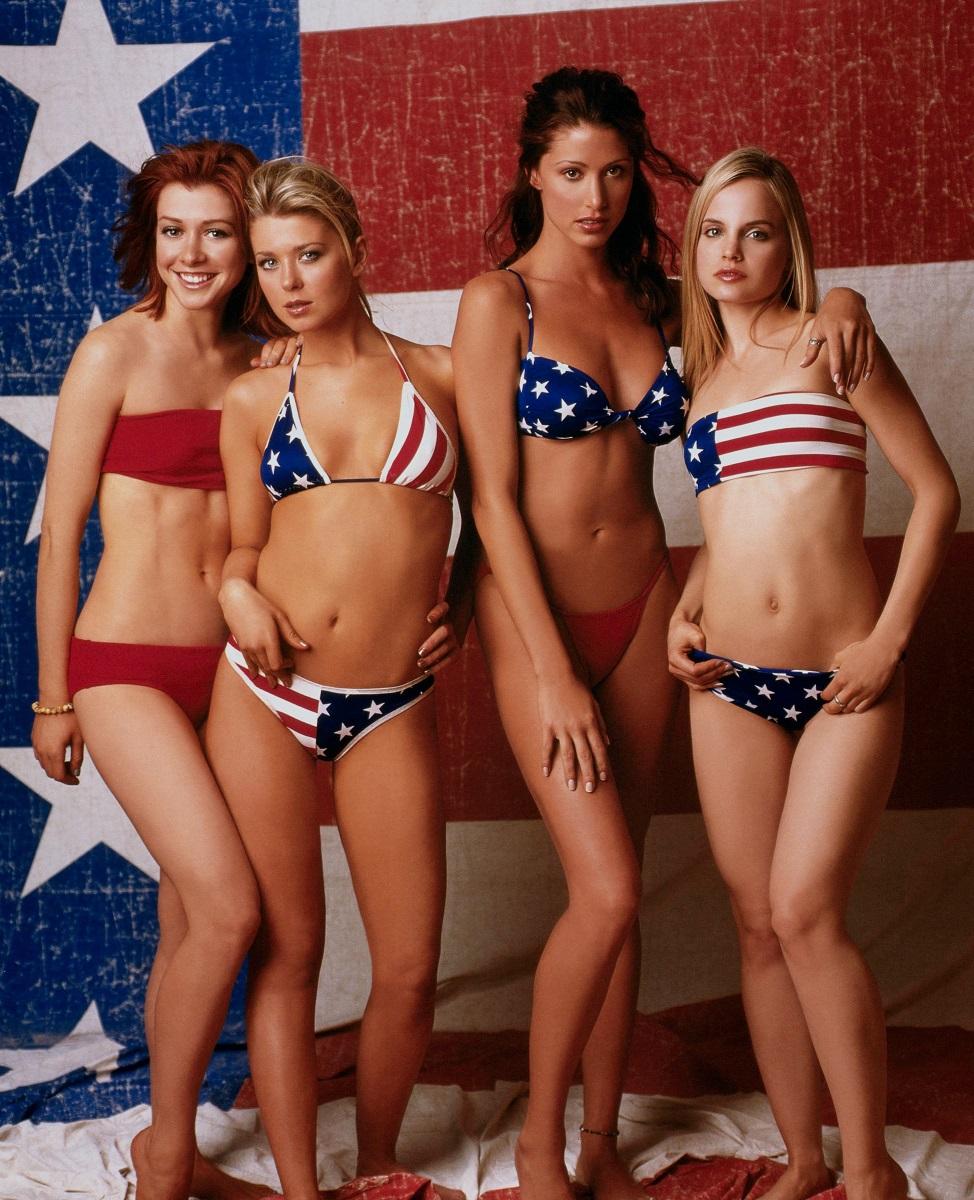 Mena Suvari, Tara Reid, Alyson Hannigan și Shannon Elizabeth într-un poster pentru lansarea American Pie. Toate 4 poartă costume de baie în nuanțe de roșu, albastru și alb, cu steagul Statelor Unite ale Americii pe fundal