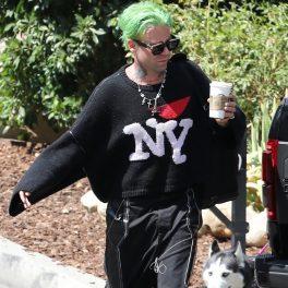 Mod Sun, îmbrăcat în negru, cu părul vopsit verde, cafea în mână, pe stradă în California
