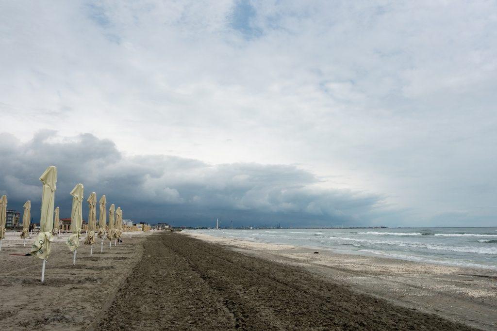 Un peisaj superb cu plaja din Năvodari pe care se află umbreluțe, în timp ce plaja este lovită de valurile mării, iar cerul este înnorat