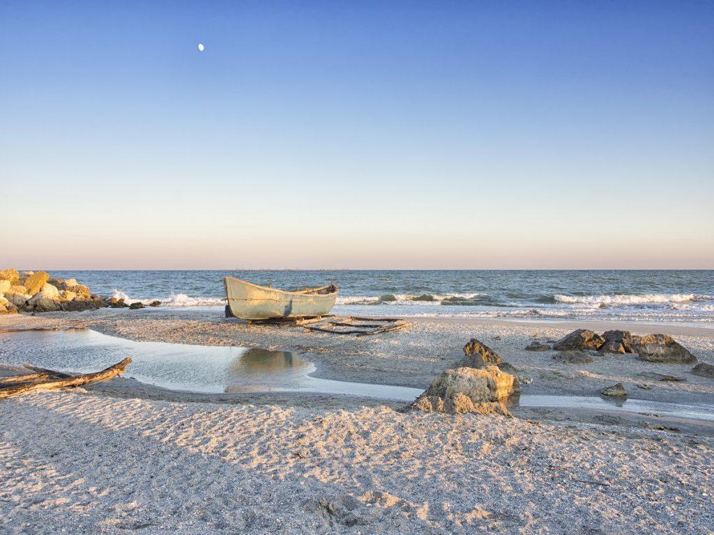 Peisaj care surprinde Plaja Corbu cu nisipul său fin și alb în timp ce este scăldată de valurile mării