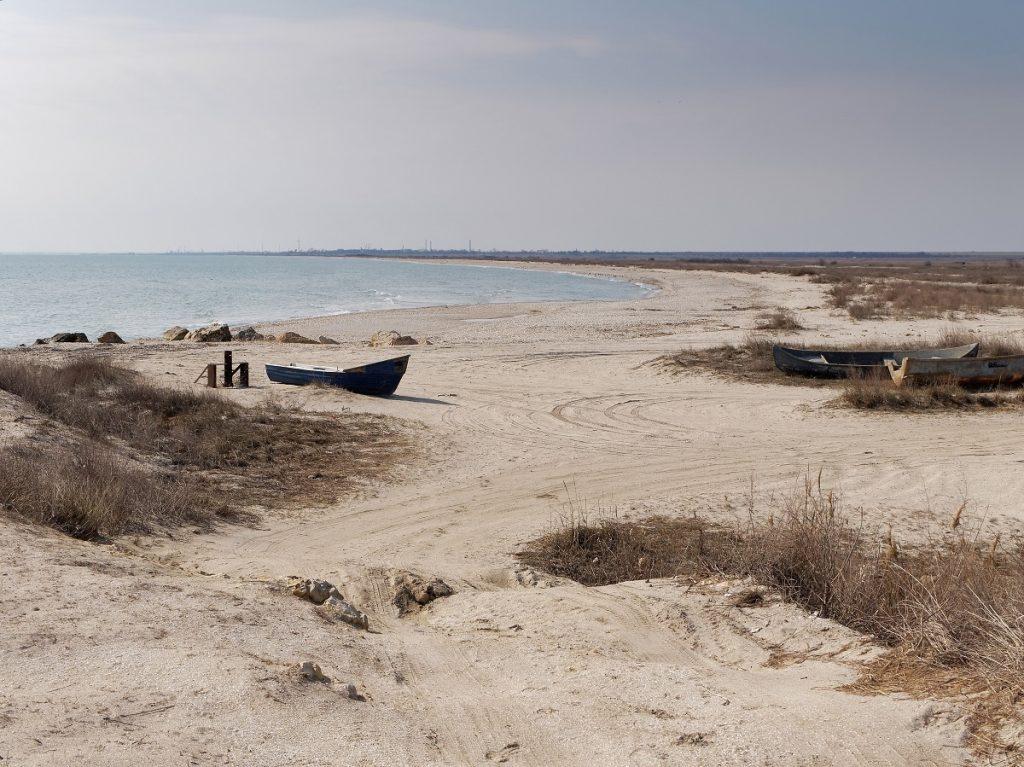 O imagine boemă în care este redată plaja Vadu cu nisipul fin și vegetația sălbatică pentru a ilustra frumusețea unei plaje mai puțin cunoscute din România