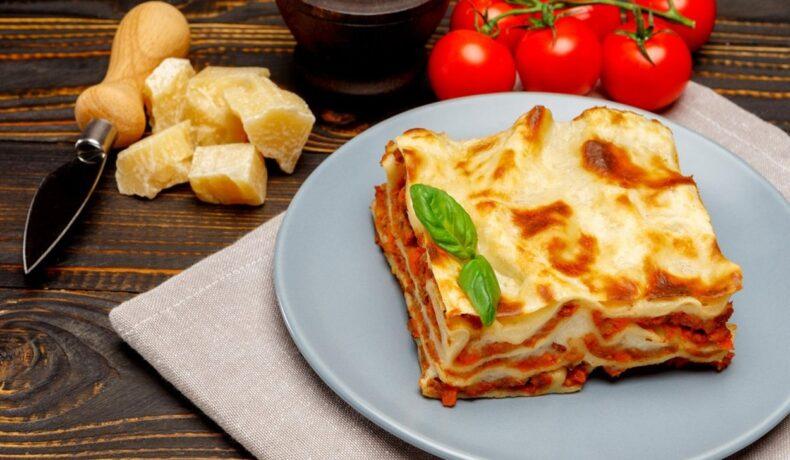 Porție de lasagna bolognese pe o farfurie gri