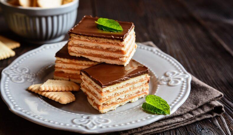 Trei porții de prăjitură fără coacere cu biscuiți și cremă caramel pe o farfurie gri