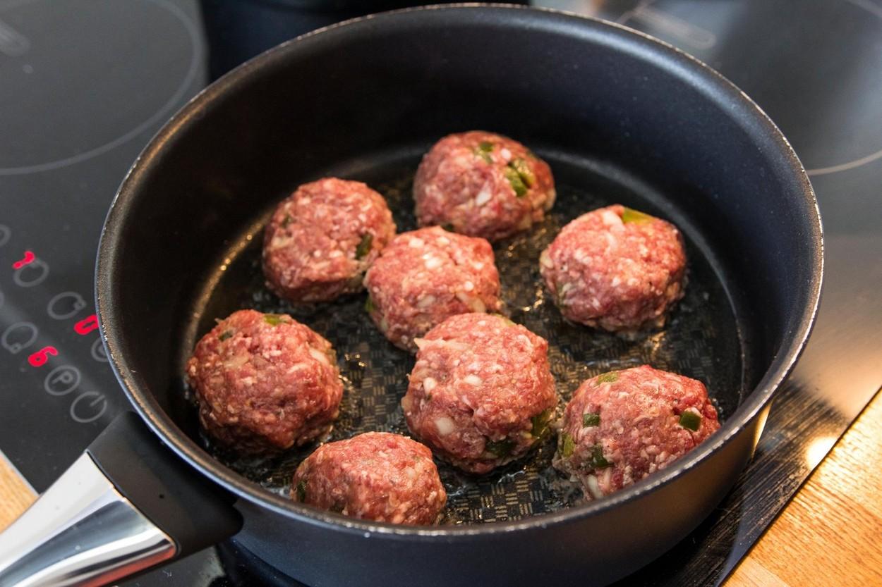 O tigaie adâncă cu ulei încins în care se află mai multe chiftele lăsate la prăjit