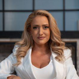 Portret al prezentatoarei Iuliana Pepene în timp ce poartă o bluză albă și un sacou și privește camera de filmat