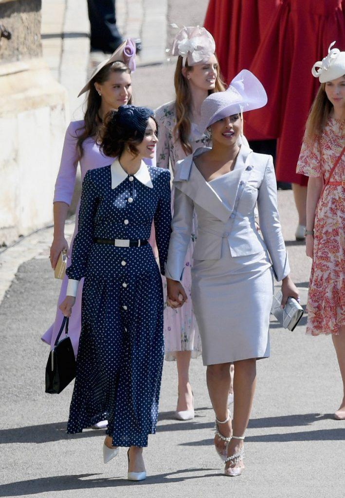 Priyanka Chopra și o prietenă la nunta lui Meghan Markle și Prințul Harry. A îmbrăcat un compleu argintiu, cu o pălărie imensă în aceeași culoare. A fost surprinsă alături de ceilalți invitați în afara bisericii