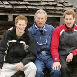 Printii Charles, Harry, William, în vacanța de ski din Elveția, Klosters, în 2005. Toți 3 îmbrăcați în costume de ski, cu zăpadă și o cabană în spate