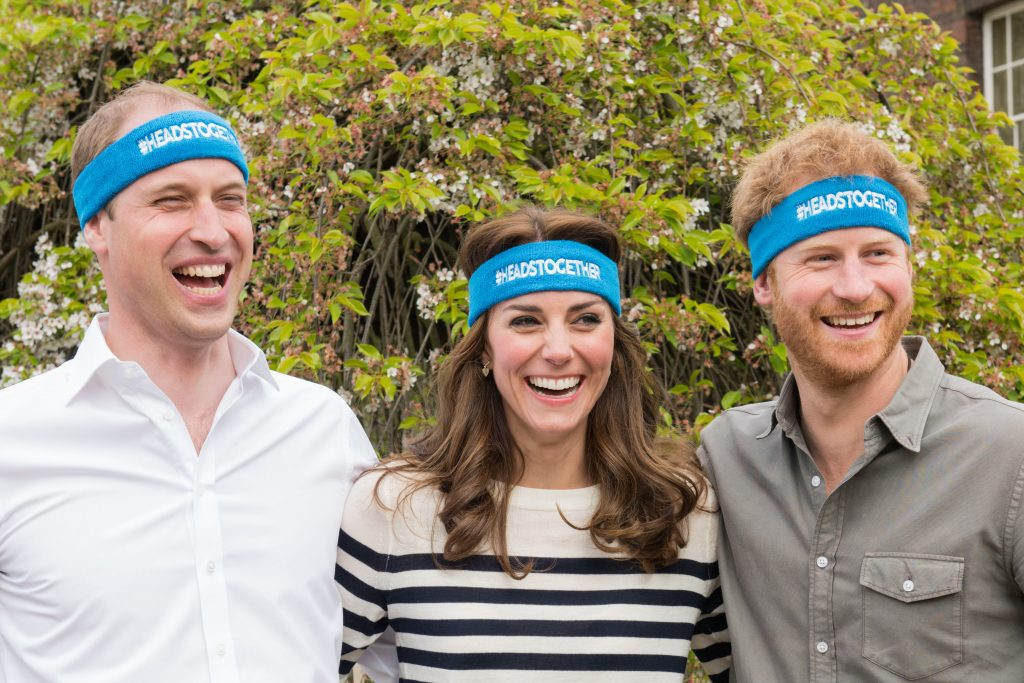 Prințul William, Prințul Harry, Kate Middleton în campania Heads Together, 2016. Toți trei au bentițe albastre pe cap, cu logo-ul campaniei. William poartă o bluză albă, Kate poartă o bluză cu dungi albe și negre și Harry poartă o cămașă neagră. Fundal cu verdeață