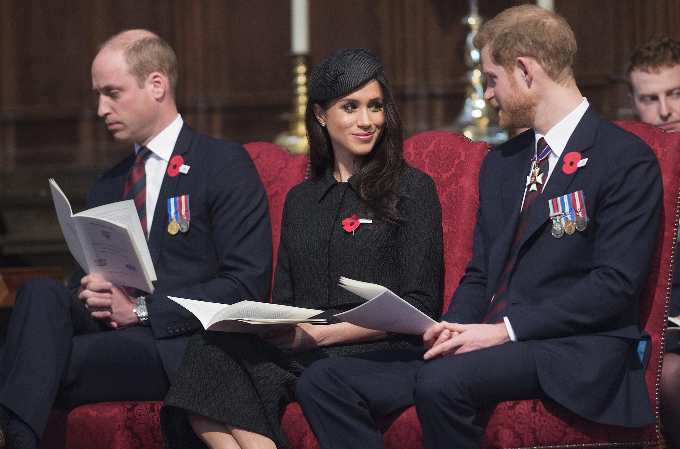 Prințul William, Prințul Harry, Meghan Markle, Anzac Day 2018, în Westminster Abbey. Toți trei s-au îmbrăcat în negru și stau pe scaune roșii