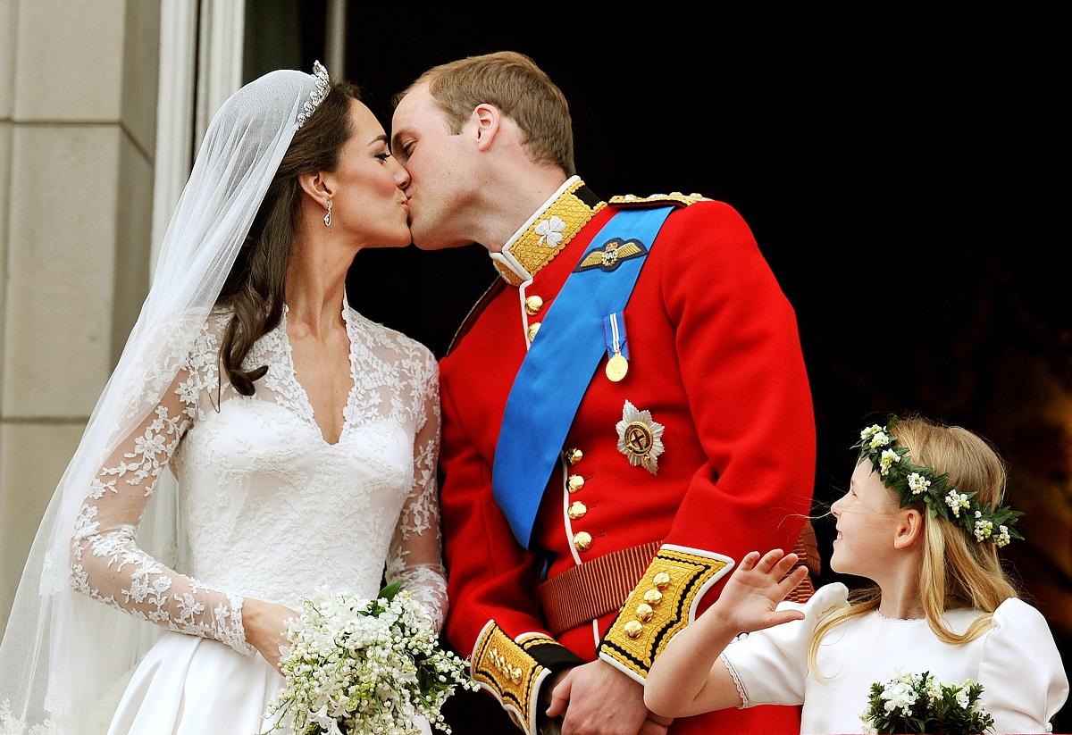 Kate Middleton și prințul William în ziua nunții din anul 2011, sărutul pe balcon după ceremonei. Ea în rochie de mireasă, el în uniforma roșie.