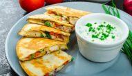 Quesadilla cu pui și legume alături de sos și ceapă verde, gata de servit