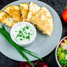 Quesadilla cu pui și legume porționată pe un platou gri, alături de sos alb