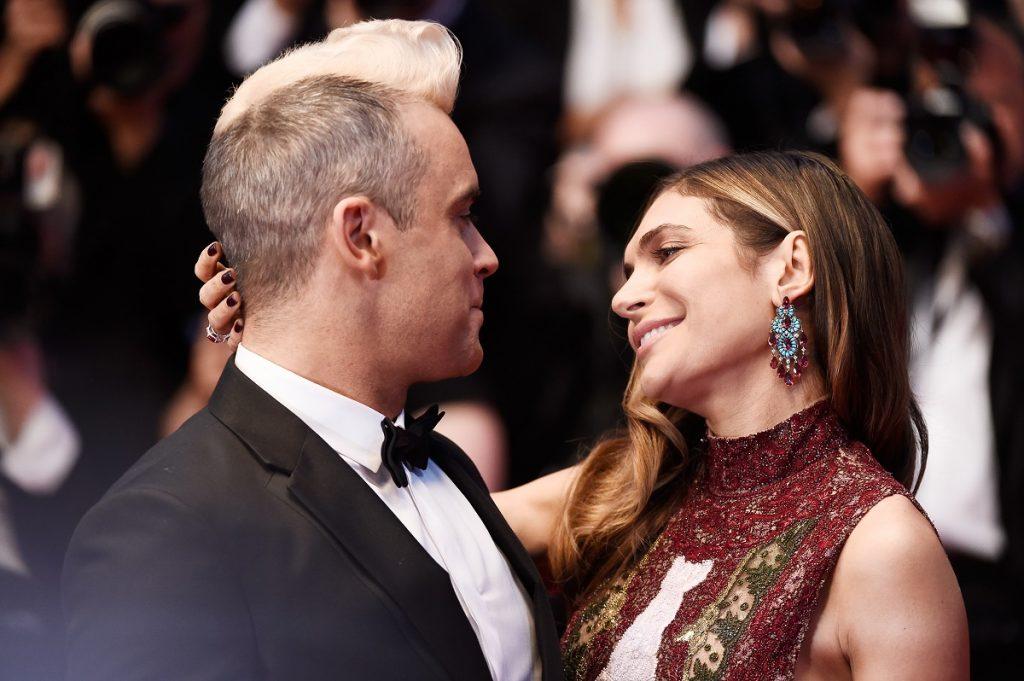 Robbie Williams și Ayda Field pe covorul roșu de la Festivalul de Film de la Cannes, 2015. S-au uitat iubitor în ochii celuilalt. El îmbrăcat în costum negru, ea în rochie roșu închis