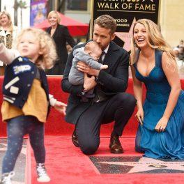Ryan Reynolds și Blake Lively, plus două dintre fiicele lor, în decembrie 2016, când el a primit o stea pe Hollywood Walk of Fame. Reynolds e îmbrăcat într-un costum negru și Lively poartă o rochie albastră, cu decolteu. Fundalul e roșu