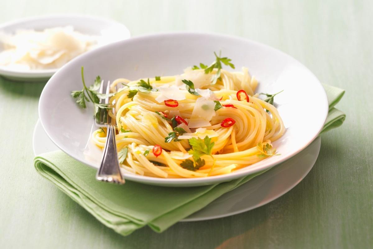 Spaghete aglio e olio într-o farfurie albă cu furculiță