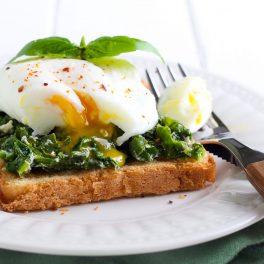 Spanac cu usturoi și lămâie, servit cu ouă poșate, pe o felie de pâine