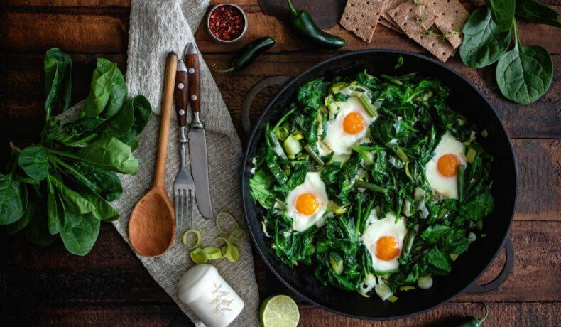 Spanac cu usturoi și lămâie și ouă ochiuri, așezate într-o tigaie, pe o masă de bucătarie.